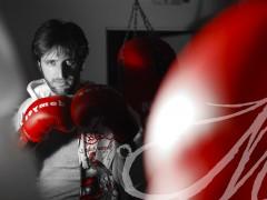 Fotografía del reflejo de un hombre en e espejo con los guantes junto al saco de boxeo
