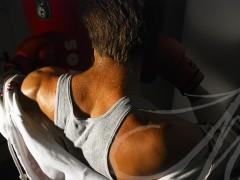 Fotografía de la espalda de un hombre, detalle del sudor, mientras boxea