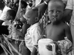Fotografía de viaje, Costa de Marfil. Niños negritos observan un evento público