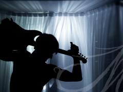 Fotografía de la silueta de un hombre con una guitarra sobre su hombro bajo la luz azul de una ventana, de noche.