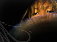 Fotografía del detalle de los ojos de una mujer tras una lampara de hilos de luz azul