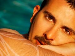 Fotografía de retrato de hombre. Primer plano del rostro de un chico apoyado en el borde de la piscina