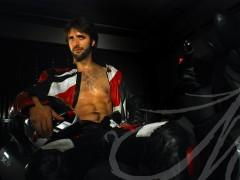 Parte del book de Willy, donde posa sobre la moto vestido con el traje de cuero y casco sobre las piernas