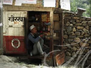 Fotografía social de viajes. Nepal. Hombre mayor con tapi regenta un minúsculo quiosco mientras fuma