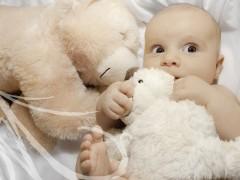 Fotografía de una bebé de cinco meses entre peluches