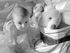 Fotografía en blanco y negro de un bebé a cuatro patitas junto a peluches