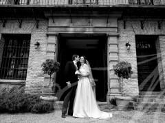 Fotografía de boda. Novios delante de la puerta de la casa de la finca.